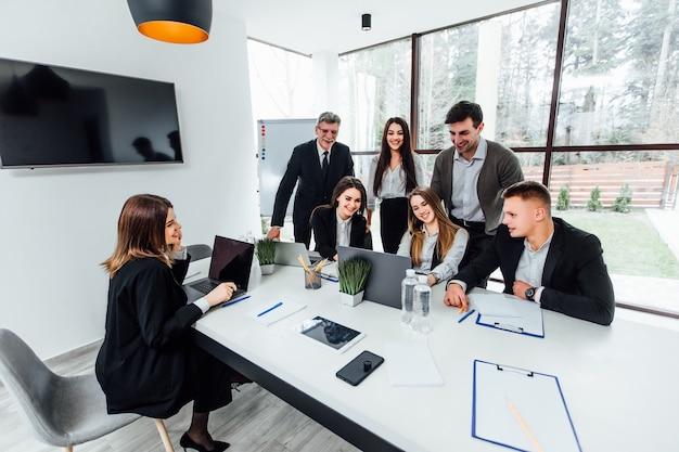 Jovens empresários digitando em um laptop e escrevendo na sala de conferências.