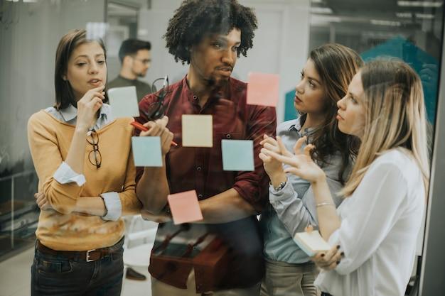 Jovens empresários discutindo em frente a parede de vidro usando post-it notes e adesivos