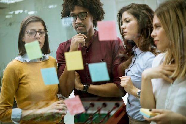 Jovens empresários discutindo na frente da parede de vidro usando post-it notes e adesivos