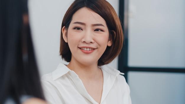 Jovens empresários e empresárias asiáticos felizes se encontrando com ideias novas