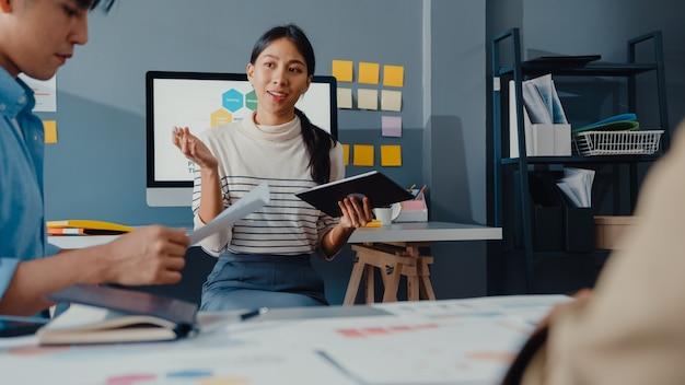 Jovens empresários e empresários asiáticos felizes se reunindo com ideias novas sobre o projeto