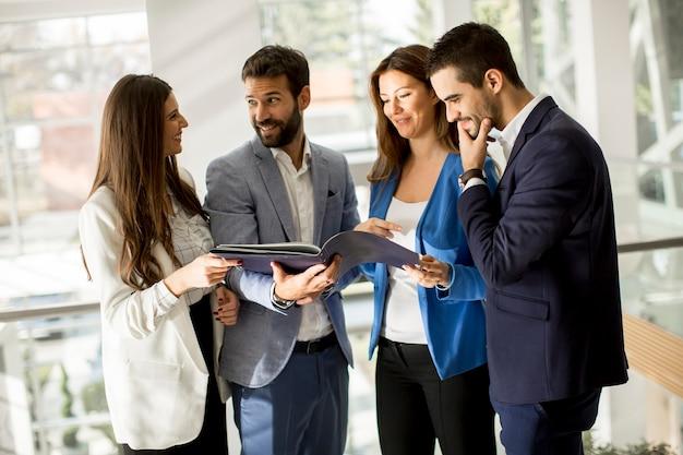 Jovens empresários em pé e analisando documentos