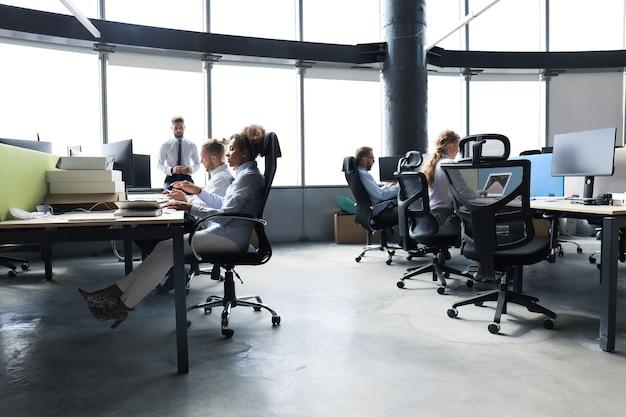 Jovens empresários em trajes formais usam tecnologia moderna enquanto trabalham no escritório.