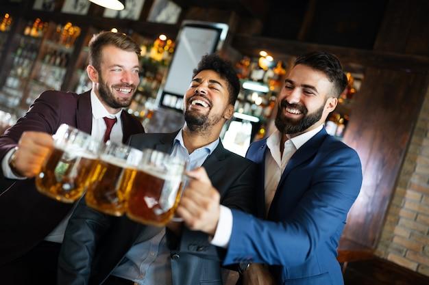 Jovens empresários estão bebendo cerveja, conversando e sorrindo enquanto descansam no bar