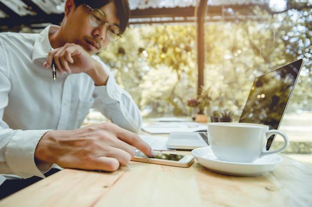 Jovens empresários estão tocando smartphones com concentração.