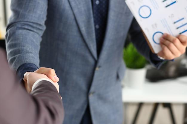 Jovens empresários felizes têm reunião no escritório apertem as mãos uns com os outros closeup