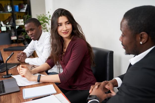 Jovens empresários felizes trabalhando juntos no escritório moderno, conceito multiétnico de trabalho em equipe