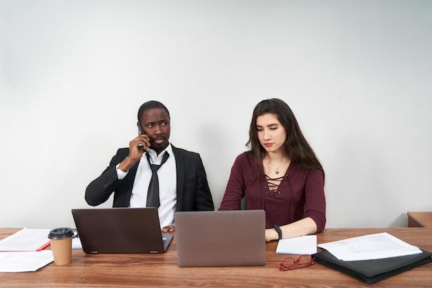 Jovens empresários felizes trabalhando juntos no escritório moderno, trabalho em equipe multiétnico. homem chamando com smartphone