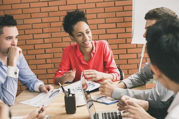 Jovens empresários interraciais, prestando atenção ao seu amigo na discussão em grupo