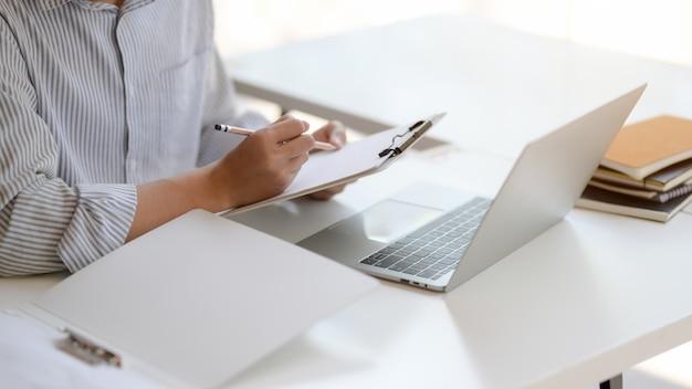 Jovens empresários masculinos trabalhando com laptop e arquivo de documento