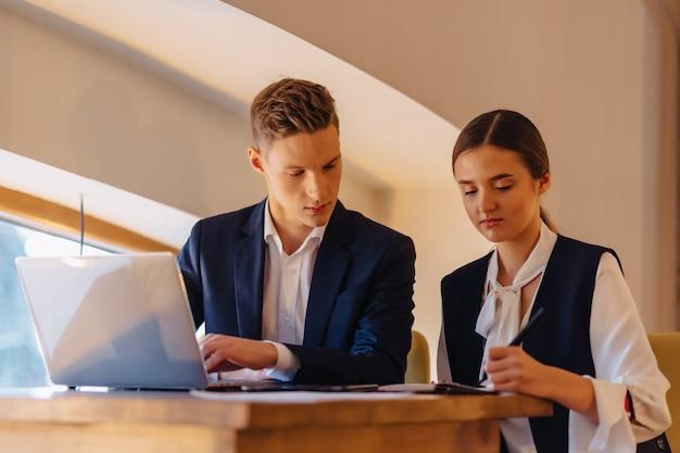 Jovens empresários menino e menina trabalham com um laptop, um tablet e notas no café