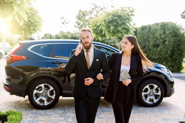 Jovens empresários, mulher bonita, de mãos dadas com seu parceiro de negócios, homem bonito com telefone, andando e conversando na rua, na frente do crossover de carro preto