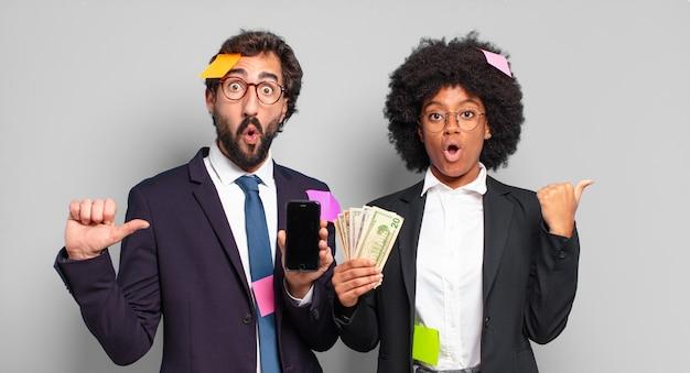 Jovens empresários parecendo surpresos de descrença, apontando para um objeto ao lado e dizendo uau, inacreditável
