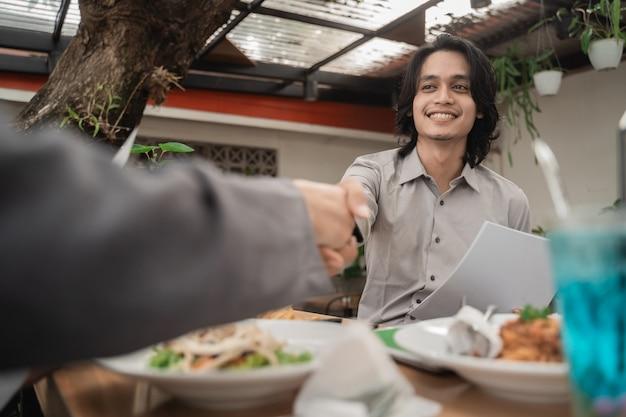 Jovens empresários se encontrando e apertando as mãos em um café