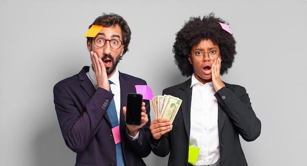 Jovens empresários se sentindo chocados e assustados, parecendo aterrorizados com a boca aberta e as mãos nas bochechas. conceito de negócio humorístico