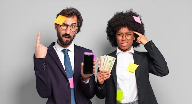 Jovens empresários se sentindo confusos e perplexos, mostrando que você é louco, louco ou maluco. humorístico