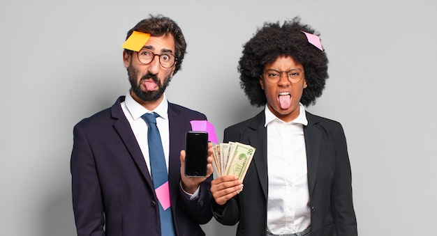 Jovens empresários sentindo-se enojados e irritados, mostrando a língua