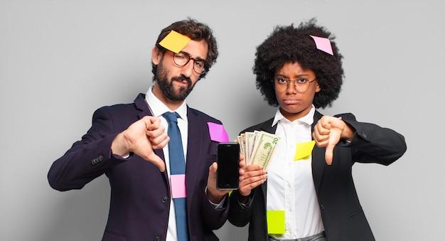 Jovens empresários sentindo-se zangados, irritados, aborrecidos, decepcionados ou insatisfeitos, mostrando o polegar para baixo com um olhar sério. conceito de negócio humorístico