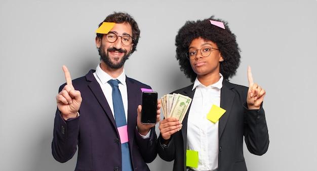 Jovens empresários sorrindo e parecendo simpáticos, mostrando o número um ou primeiro com a mão para a frente, em contagem regressiva. conceito de negócio humorístico
