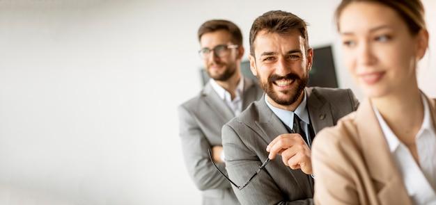 Jovens empresários sorrindo juntos em uma fila