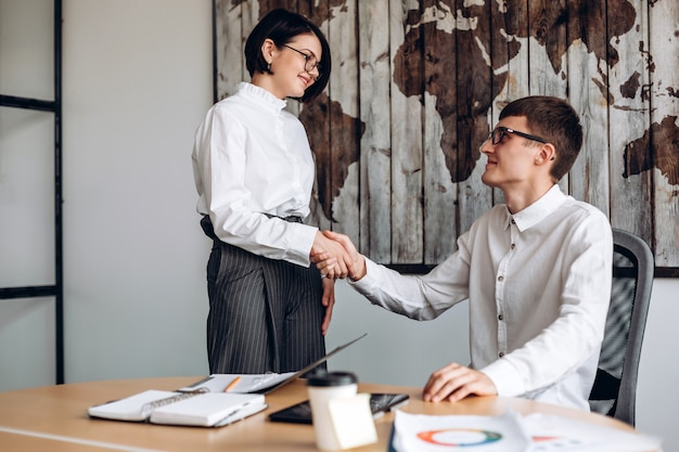 Jovens empresários têm um acordo, eles apertam as mãos