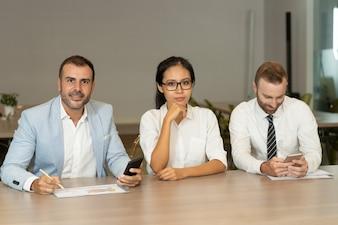 Jovens empresários trabalhando e olhando para a câmera na mesa