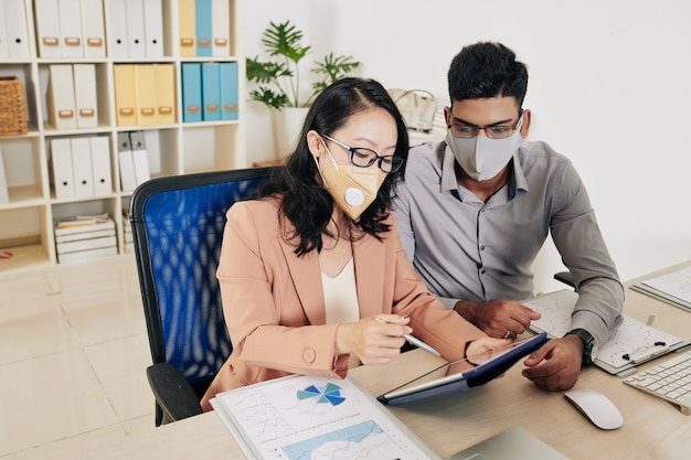 Jovens empresários usando máscaras protetoras ao discutir relatórios e plano de desenvolvimento de negócios na reunião