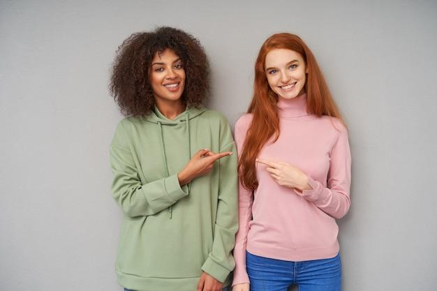 Jovens encantadoras e alegres mostrando seus dentes brancos perfeitos enquanto sorriem positivamente e apontam umas para as outras com os indicadores levantados, posando sobre uma parede cinza