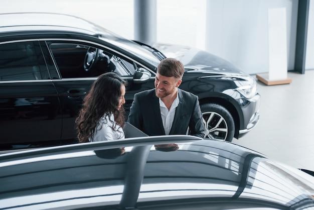 Jovens encantadores. cliente do sexo feminino e empresário barbudo elegante moderno no salão automóvel