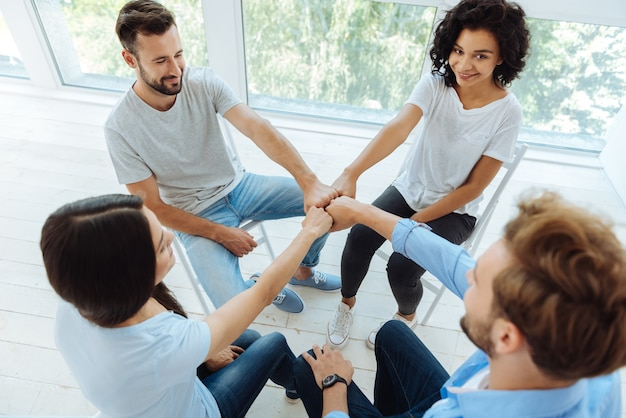 Jovens encantados positivos sentados em círculo e sorrindo enquanto juntam os punhos