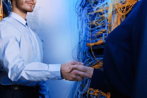 Jovens engenheiros apertando as mãos na sala do servidor