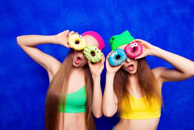 Jovens engraçadas com chapéus segurando donutes doces como óculos