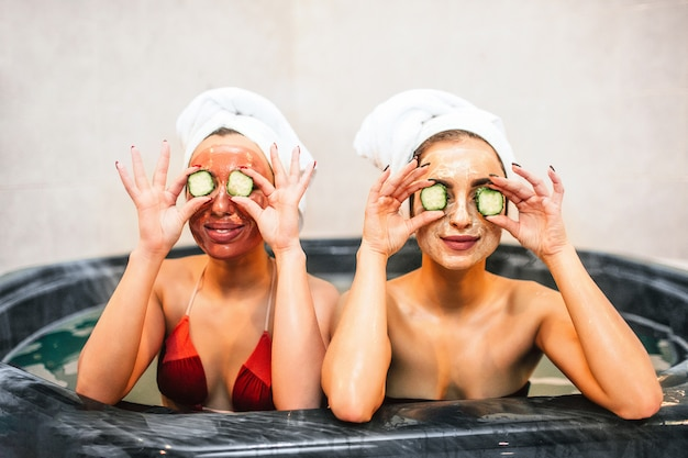 Jovens engraçadas sentam-se no banho de hidromassagem e seguram pedaços de pepino nos olhos. eles têm procedimentos de beleza e spa no quarto. modelos parecem felizes.