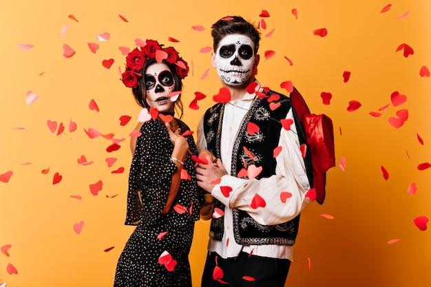 Jovens engraçados dançando na festa latina no halloween. casal com roupas de baile de máscaras, posando na parede amarela.