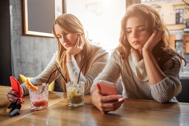 Jovens entediadas sentam à mesa. eles seguram telefones e olham para ele. modelos têm copos com bebida na mesa.