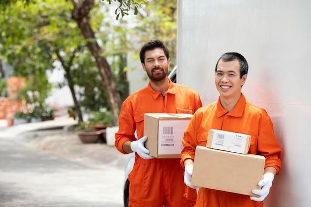 Jovens entregadores movendo várias caixas de pacotes