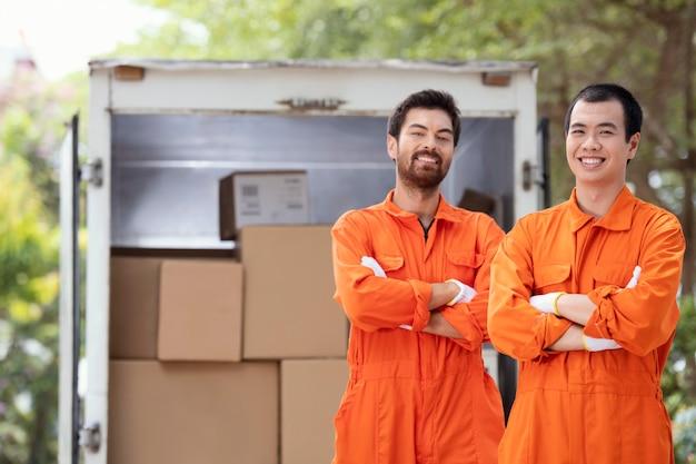 Jovens entregadores perto de carro de entrega