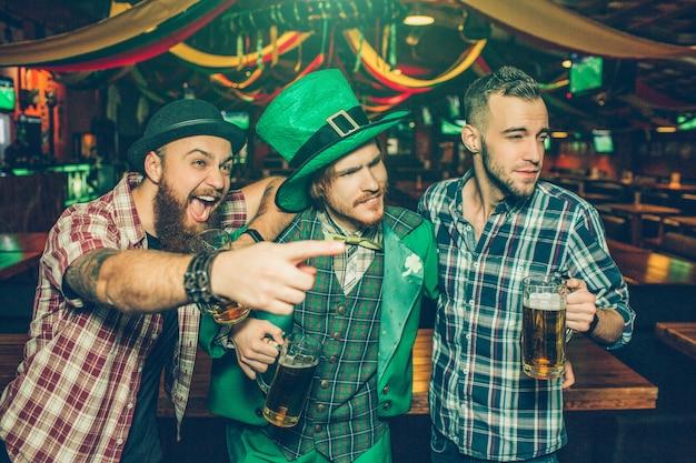 Jovens entusiasmados estão juntos no pub. cara no ponto esquerdo. eles olham para a direita. jovem de terno verde usar fantasia de são patrício.