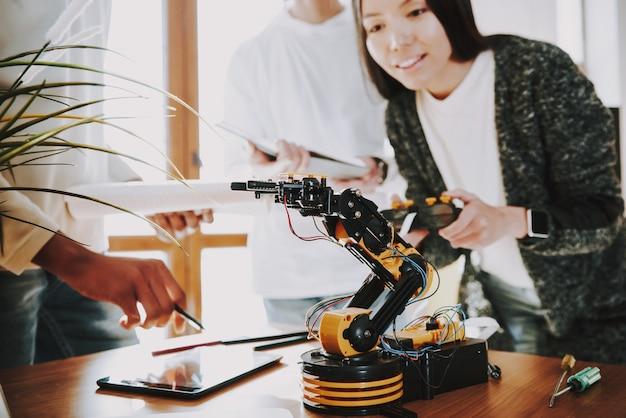 Jovens especialistas com robô no trabalho.