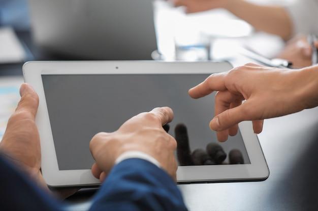 Jovens especialistas em consultoria com tablet em ambientes fechados