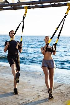 Jovens esportivos treinando com trx perto do mar pela manhã.