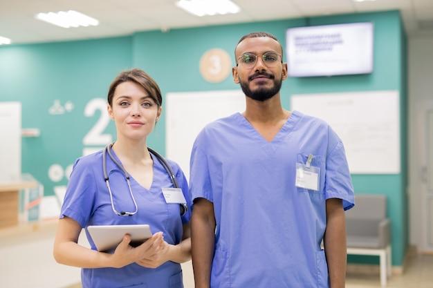 Jovens estagiários interculturais de sucesso de uniforme em pé na frente da câmera enquanto trabalham em clínicas modernas