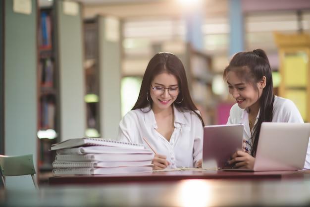Jovens estudantes aprendendo, estantes de biblioteca