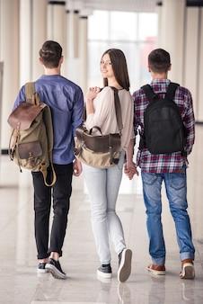 Jovens estudantes atraentes descendo o corredor na faculdade