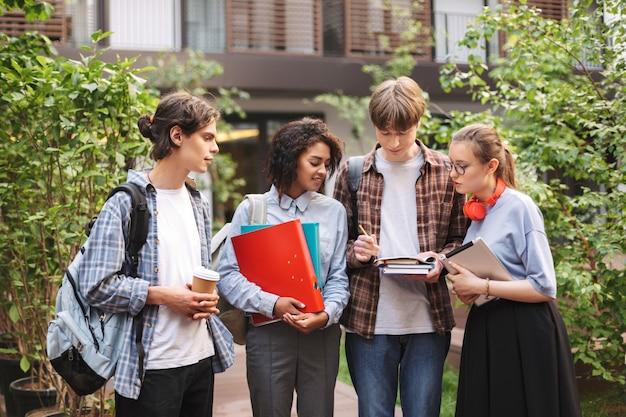 Jovens estudantes com livros e pastas nas mãos e fazendo anotações em um caderno enquanto passam algum tempo juntos no pátio da universidade