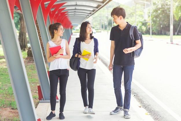 Jovens estudantes conversando e andando na escola. volta ao conceito de escola. educação e estudo.