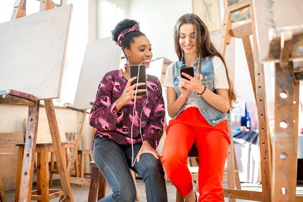 Jovens estudantes criativos de várias etnias sentados com telefones durante o intervalo para pintar no estúdio da universidade