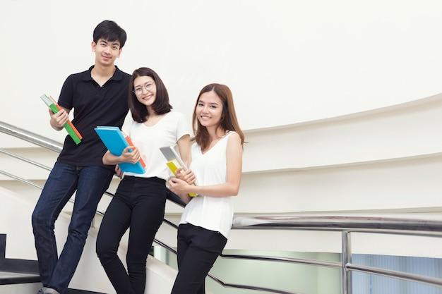 Jovens estudantes em pé com segurando livros na biblioteca.