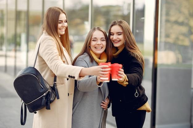 Jovens estudantes em um campus de estudantes em pé com um café