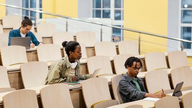 Jovens estudantes frequentando uma aula na universidade
